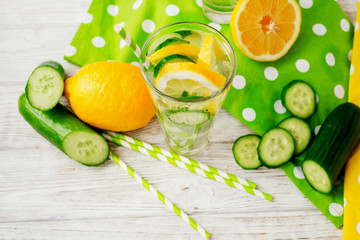 detox , healthy and refreshing drink ,Nutritious cold sparkling water with fresh green cucumber and yellow lemon on a wooden background