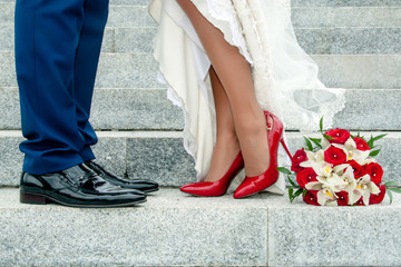Legs of wedding couple and bouquet