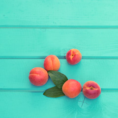 Fresh homegrown apricots on pastel blue wooden table