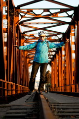 girl standing on the rails in a helmet