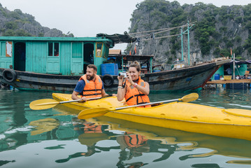 Couple rowing kayak at foggy sea in Halong Bay.
