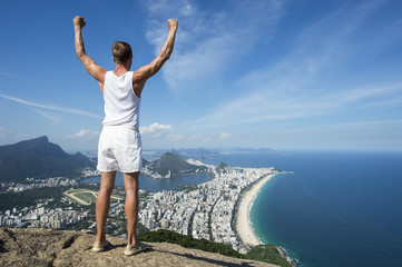 Athlete in vintage white uniform stands with arms punching the air in celebration at an overlook view of the Rio de Janeiro Brazil skyline