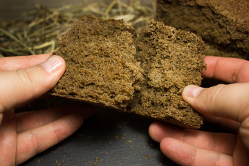 Black rye bread in hands on a background of hay.