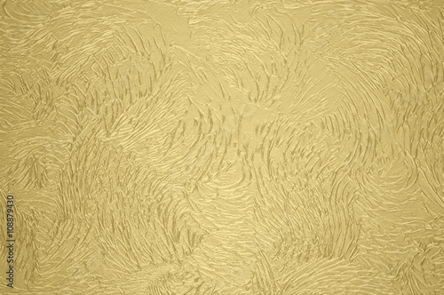 Stucco style artex wall coating background in gold colour\