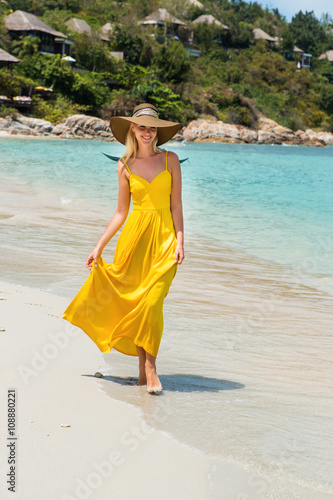 Carefree beautiful fashion blonde woman in beach straw hat holding her long  yellow dress and walking 7a30726f397b