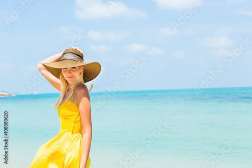 Carefree beautiful fashion blonde woman in beach straw hat and long yellow  dress flying in the d7395d1636dc