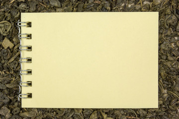 Dry green tea, a blank sheet of paper. Place for text