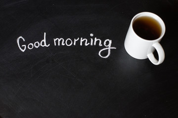 cup of hot tea on a black board and text good morning