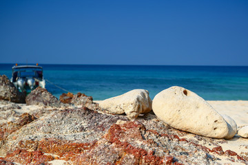 sea and sand with white stone on blue sky