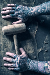 Hammer in the tattoed hands