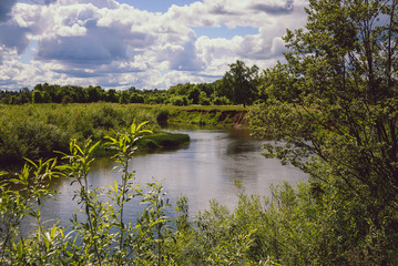 Green field with river under blue sky in summer, Russia.