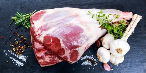 Raw lamb leg on blue stone background
