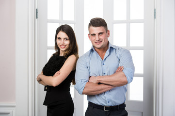 Business couple is standing together and smiling in the doorway home interior loft office