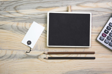 top view photo school and business supplies on wooden table. pen, chalkboard,paper,calculator