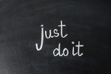just do it, handwritten with white chalk on a blackboard. Motivational phrase