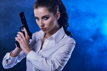 beautiful sexy girl holding gun . smoke background