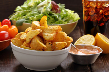 Roasted potatoes with dip and fresh salad on wooden table