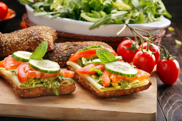Vegetarian sandwich with pesto on wooden background