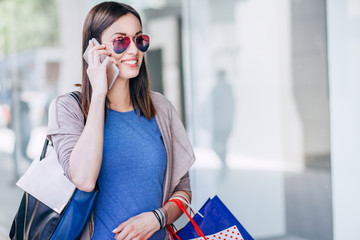 Beautiful young women shopping and using a smart phone/ Woman is using a smart phone while she is shopping in the city.
