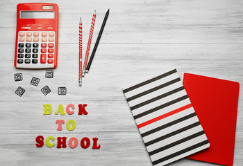 School set with back to school inscription, notebooks and calculator on light wooden background
