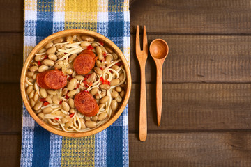Traditional Chilean dish called Porotos con Riendas (English: beans with reins), made of cooked beans, linguine (flat spaghetti) and served with fried sausage, photographed on wood with natural light