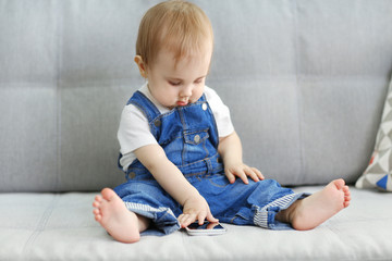 Baby sitting on sofa and playing with smartphone