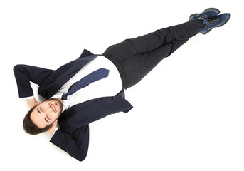 Young tired businessman lying on the floor