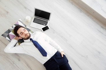 Young businessman with laptop lying on the floor