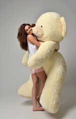 Young beautiful girl hugging big teddy bear soft toy happy smili