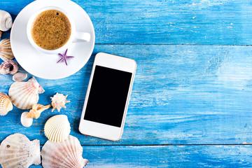 cup of coffee, shells, mobile phone on the old blue wooden boards.sea style. marine still life