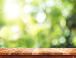 Empty brown wood table top with sun and blur green tree bokeh ba