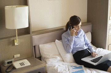 Women are talking on a mobile phone while looking at a laptop sitting on the business hotel bed