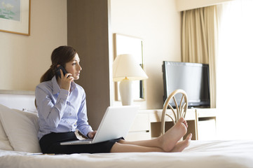 Women are talking on the phone sitting in a business hotel bed