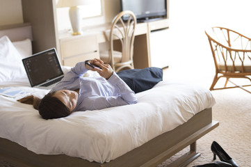Women are looking at the smartphone lying on his back in the business hotel bed