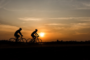 Silhouette of cycling on sunset background