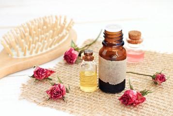 Rose essential oil, rose water, hair brush. Aromatic herbal essences hair care.