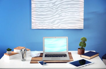 Workplace with different devices, picture and table on blue wall background