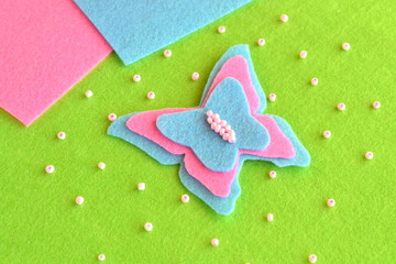 Felt butterfly on a green background, beads, blue and pink sheets. Easy children's crafts