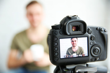 Young male blogger with cup of tea on camera screen