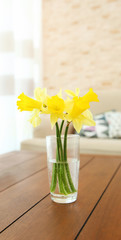 Modern living room interior. Bouquet of yellow daffodils on a table