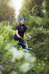 Mid-adult woman cycling through forest