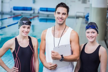 Portrait of smiling trainer and swimmers