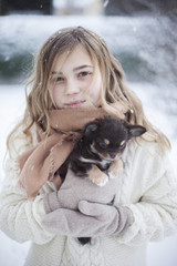 Woman holding puppy in winter scenery
