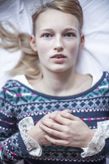 Young woman lying down on bed with hands clasped