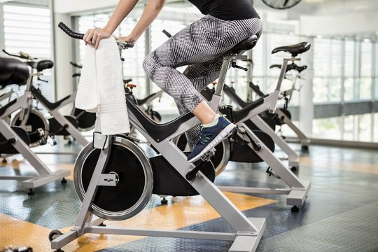 Lower section of fit woman on exercise bike
