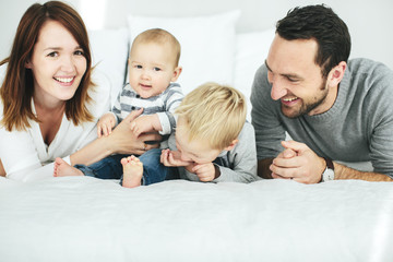 Parents with two small kids playing in bedroom