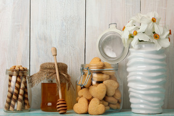 Foto op Aluminium Picknick transparent open cans of delicious cookies and a Cup of honey on wooden background near daffodils