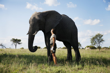 Woman standing next to elephant