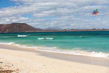 Unknown kitesurfer surfing on a flat azure water of Atlantic ocean in Corralejo, Fuerteventura, Canary islands, Spain