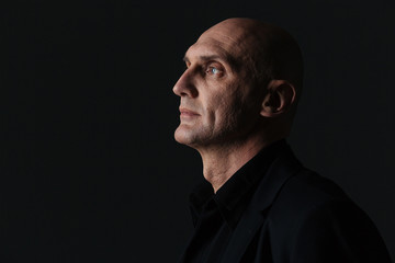 Profile of attractive boldheaded businessman in dark suit